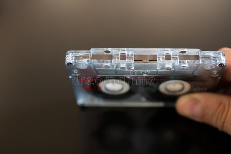 Рука держит старую магнитофонную кассету Проверите целостность магнитных животиков стоковое изображение
