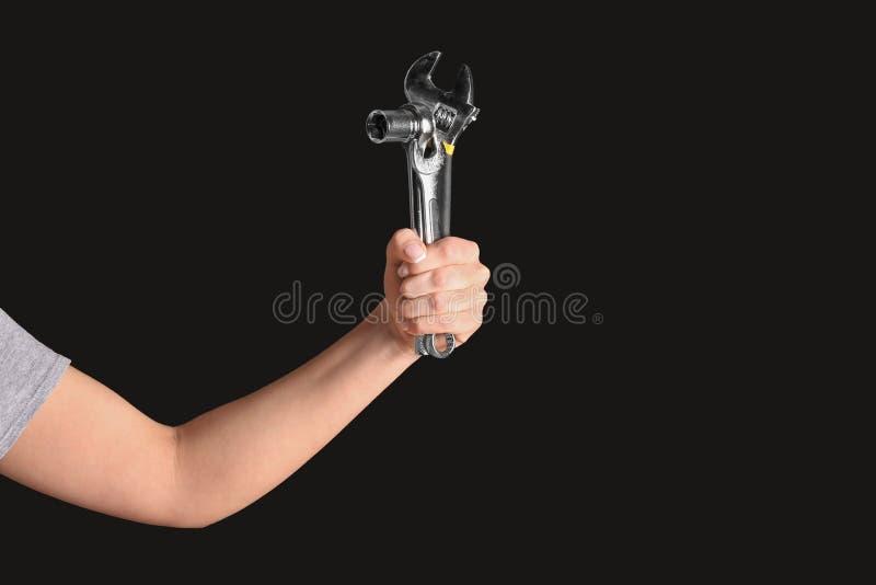 Рука женского механика автомобиля с инструментами на черной предпосылке стоковое изображение