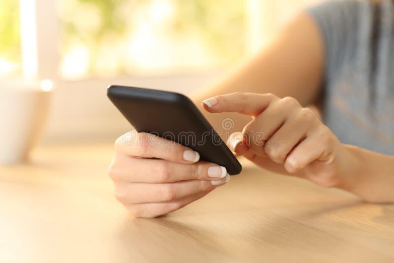 Рука женщины выбирая содержание на умном телефоне стоковое изображение rf