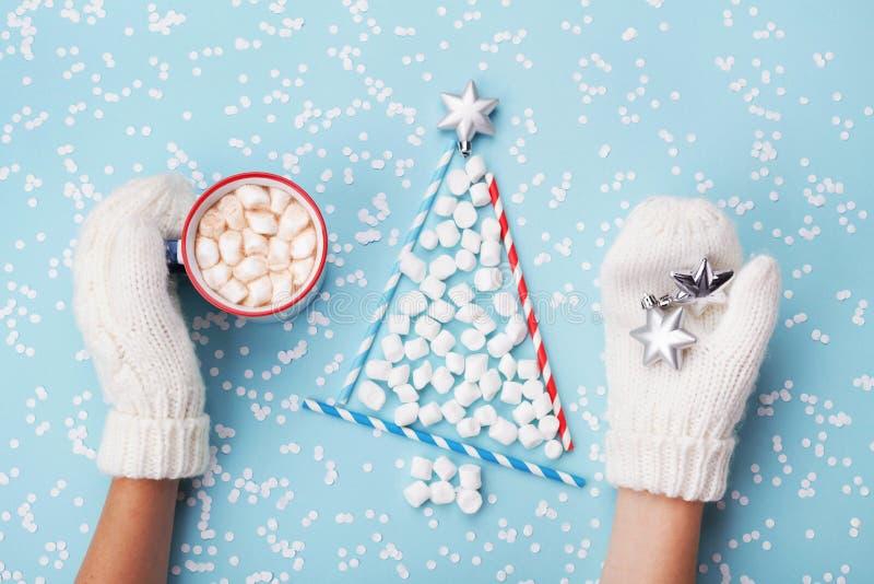 Рука женщины в чашке владением mitten горячих какао или шоколада и ели рождества сделанной из зефира на предпосылке зимы бирюзы стоковое изображение rf