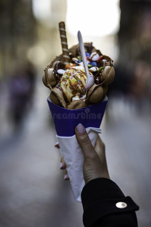 Рука женщины держа вафлю пузыря с мороженым и конфетами на голубом бумажном конусе с запачканной непознаваемой толпой на стоковое фото
