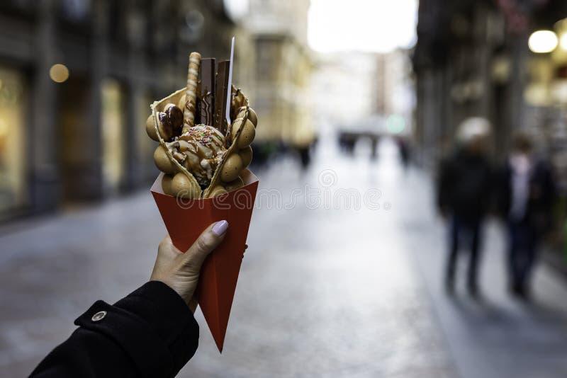 Рука женщины держа вафлю пузыря с мороженым и конфетами на красном бумажном конусе с запачканной непознаваемой толпой на стоковая фотография