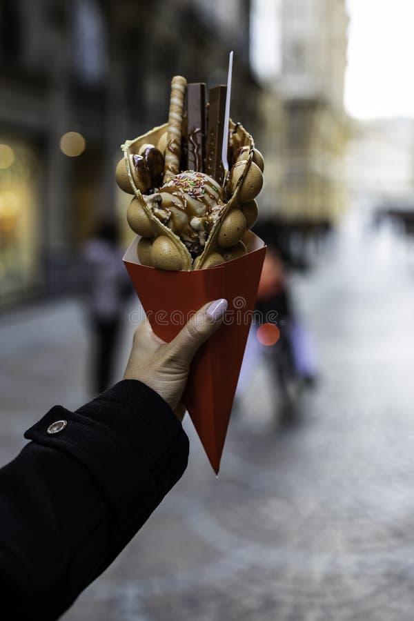 Рука женщины держа вафлю пузыря с мороженым и конфетами на красном бумажном конусе с запачканной непознаваемой толпой на стоковые фото