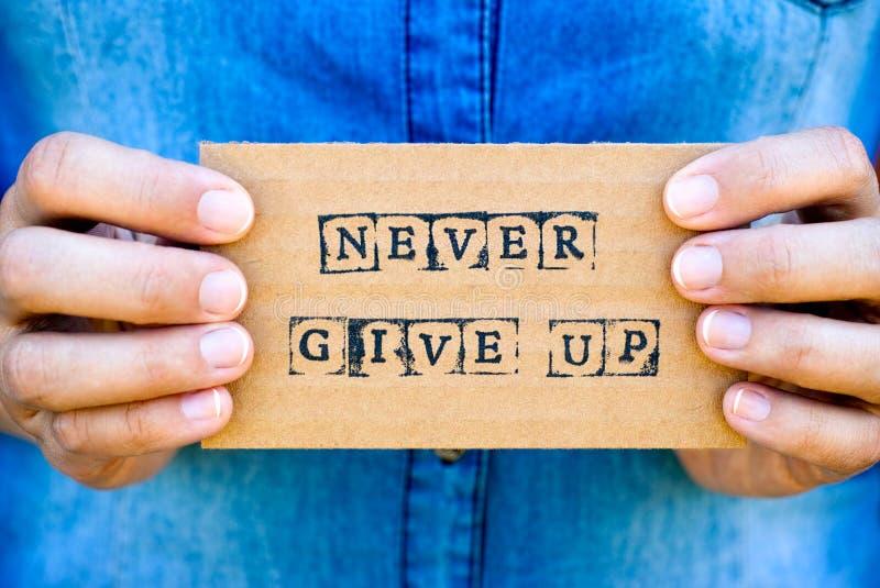 Рука женщины держа карточку картона с словами никогда не дает вверх сделанный стоковое изображение rf