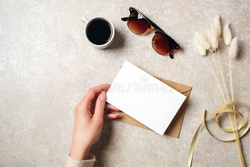 Рука женщины держа карту чистого листа бумаги над женственным столом с аксессуарами хипстера, солнечными очками, кофейной чашкой  стоковая фотография rf
