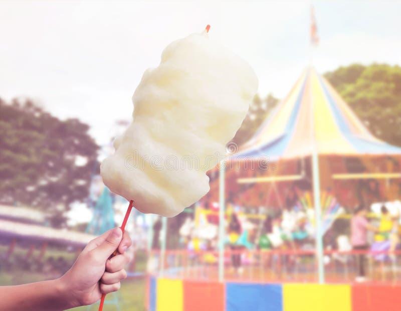Рука женщины держа конфету хлопка над предпосылкой нерезкости carousel стоковые фото