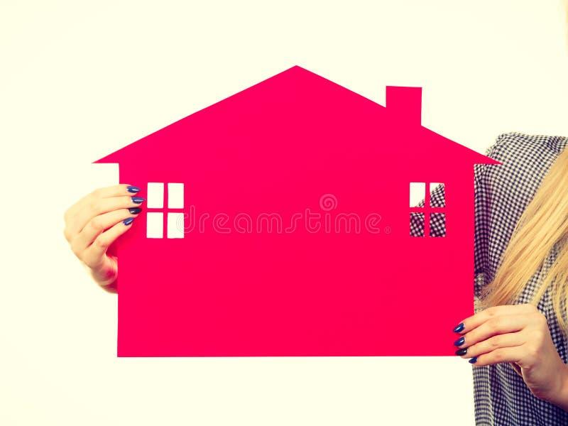Рука женщины держа красный бумажный дом стоковое фото rf