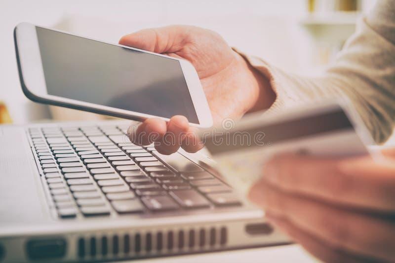 Рука женщины держа кредитную карточку и smartphone стоковая фотография