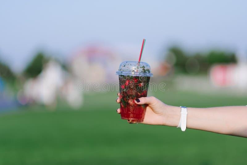 Рука женщины держа лимонад с клубниками на предпосылке парка клубника разрешения людей коктеила здоровая стоковая фотография