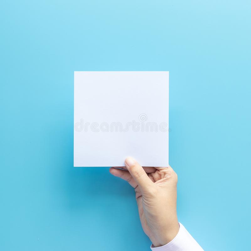 Рука женщины держа лист чистого листа бумаги изолированный на голубой предпосылке с космосом экземпляра стоковое фото rf