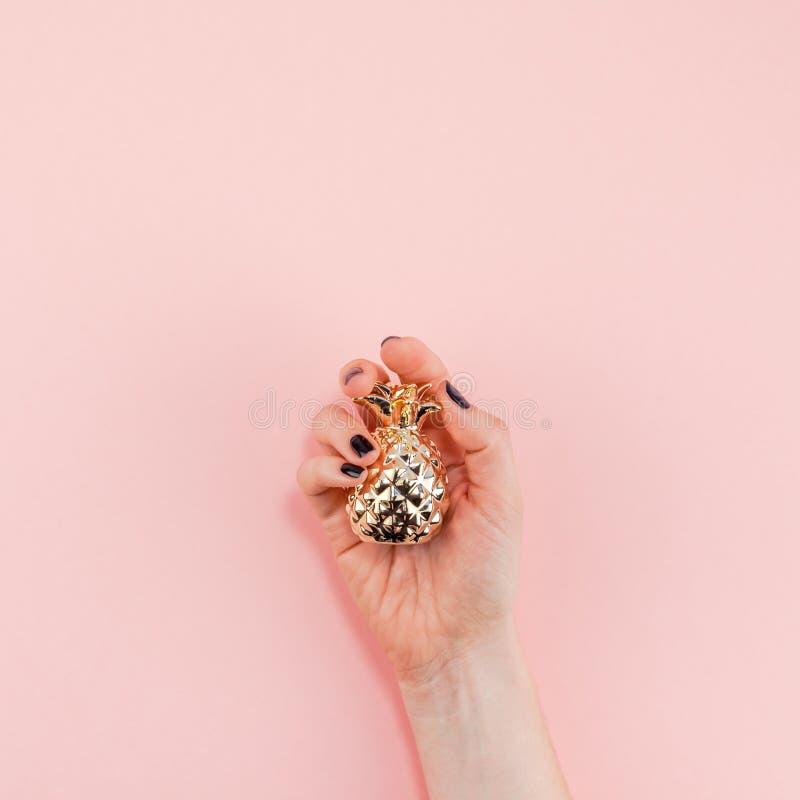 Рука женщины держа небольшой золотой ананас стоковые фотографии rf