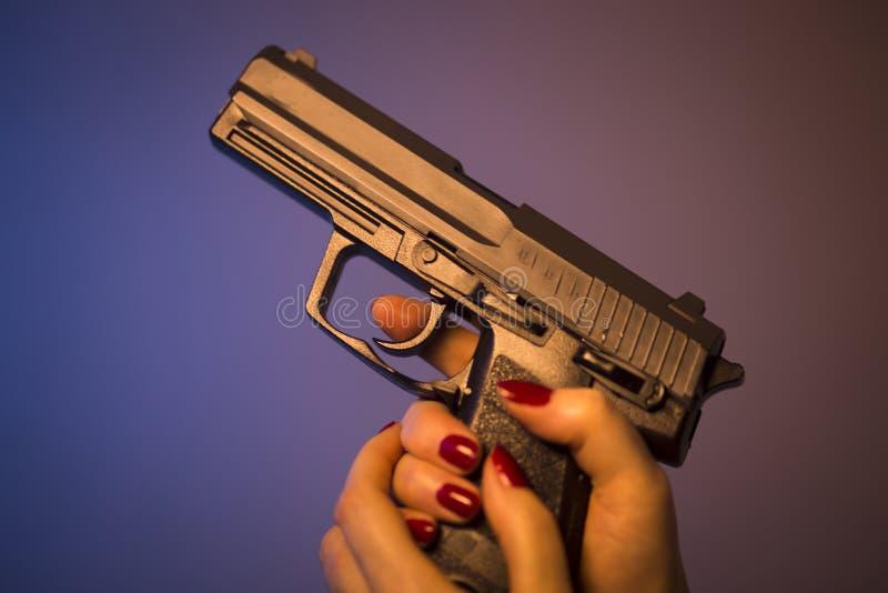 Рука женщины держа пистолет стоковое изображение
