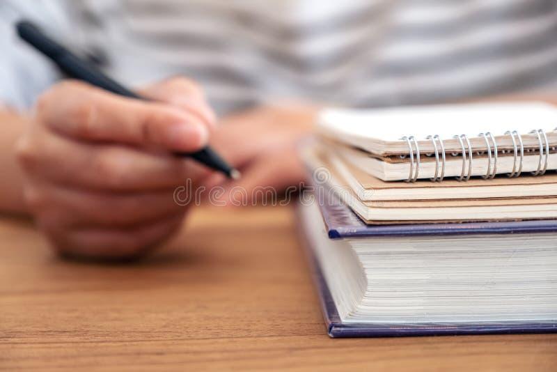Рука женщины держа ручку для записи на тетради и книгах на деревянном столе стоковое фото rf