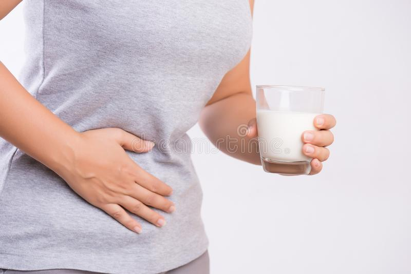 Рука женщины держа стекло молока имея плохую боль в животе из-за непереносимости лактозы проблема здоровья с продуктами питания м стоковые фотографии rf