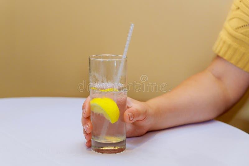 Рука женщины держа стекло соды с лимоном стоковые фотографии rf