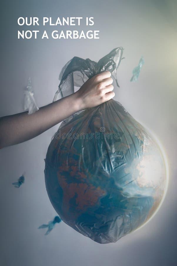 Рука женщины держа сумку отброса с глобусом земли планеты Надпись НАША ПЛАНЕТА НЕТ ОТБРОСА стоковые изображения