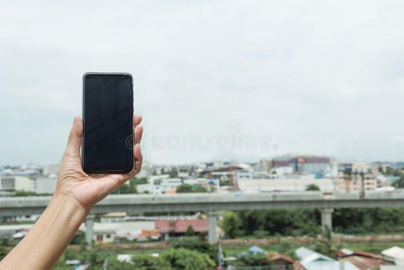 Рука женщины держа умный телефон с предпосылкой зданий стоковое фото rf