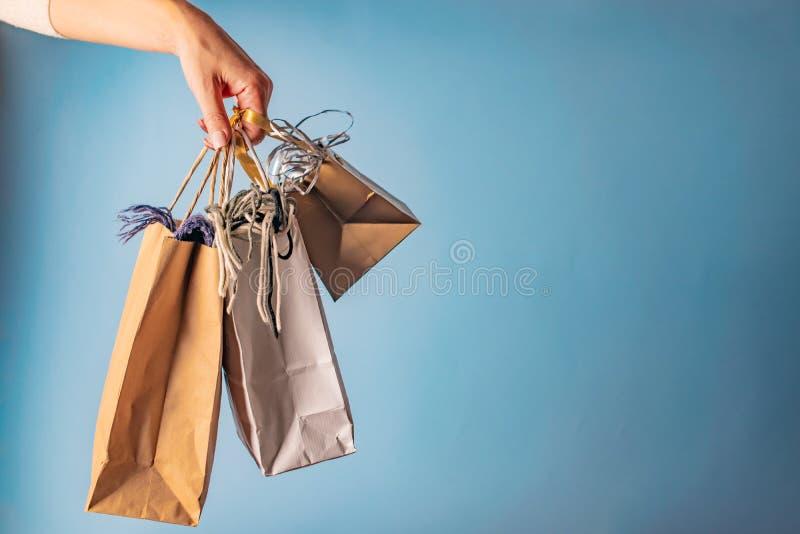 Рука женщины держа хозяйственные сумки, продажи и скидки стоковое фото rf