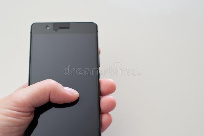 Рука женщины держа черный smartphone стоковое изображение