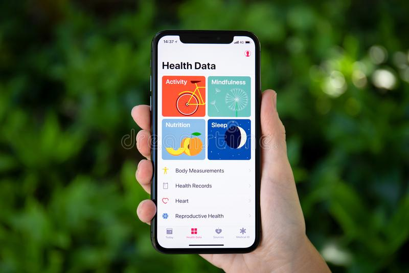 Рука женщины держа iPhone x с данными по здоровья app стоковые изображения rf
