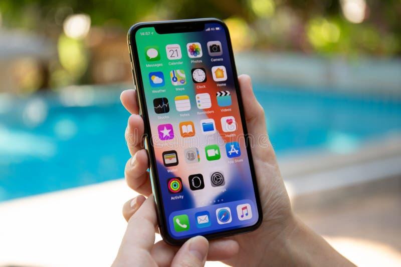 Рука женщины держа iPhone x с IOS 11 на экране стоковые фото