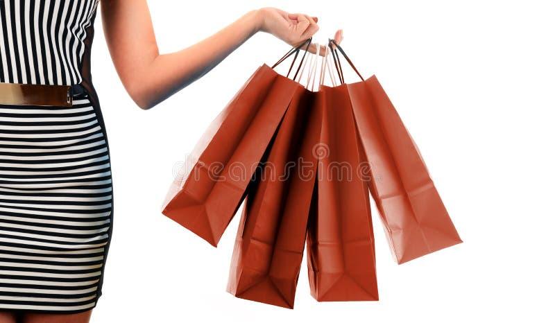 Рука женщины держа бумажные хозяйственные сумки изолированный на белизне стоковые фотографии rf