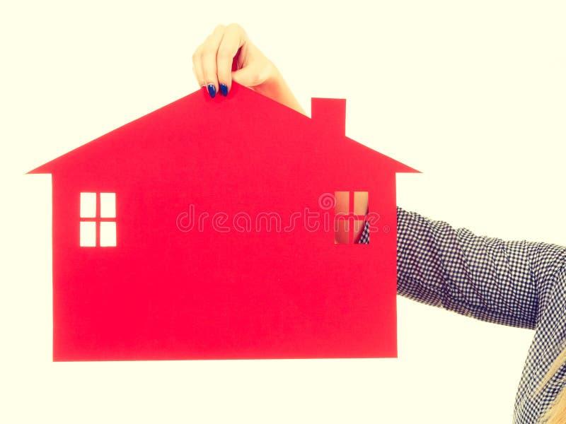 Рука женщины держа красный бумажный дом стоковые фотографии rf