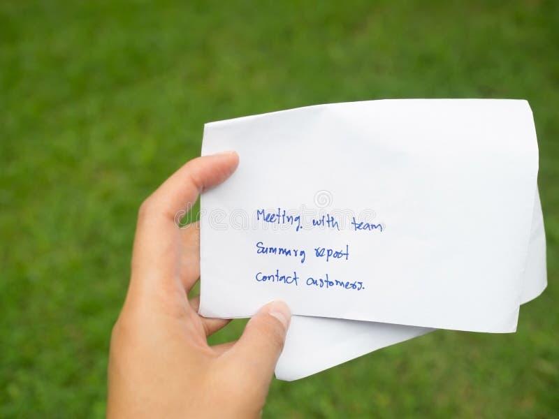 Рука женщины держа написанный белой бумагой бизнес-план дня Команда встречи, отчетный доклад и клиенты встречи в зеленой предпосы стоковые изображения rf