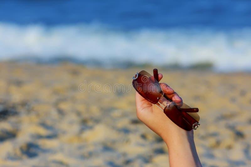 Рука женщины держа солнечные очки на тропическом пляже стоковые фотографии rf