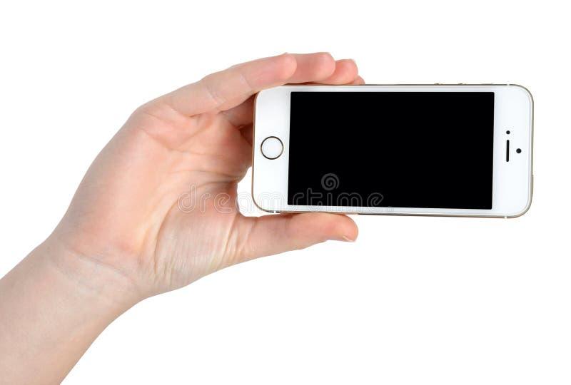 Рука женщины держа телефон iPhone 5S Яблока умный стоковая фотография