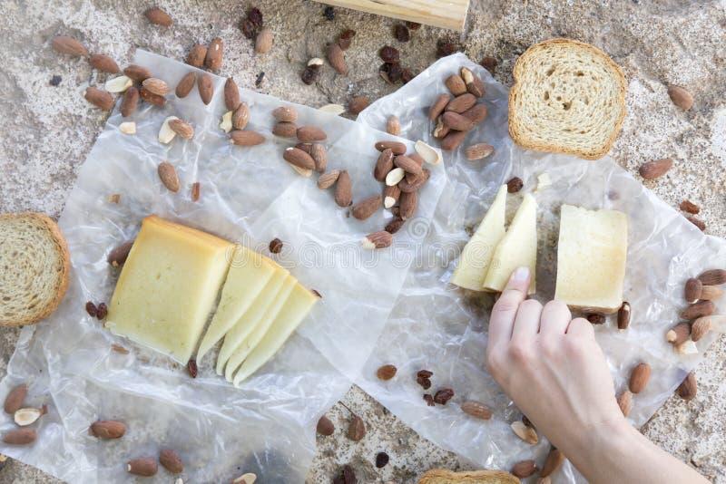 Рука женщины держа часть сыра закуски сыра, здравиц и миндалин стоковые фото