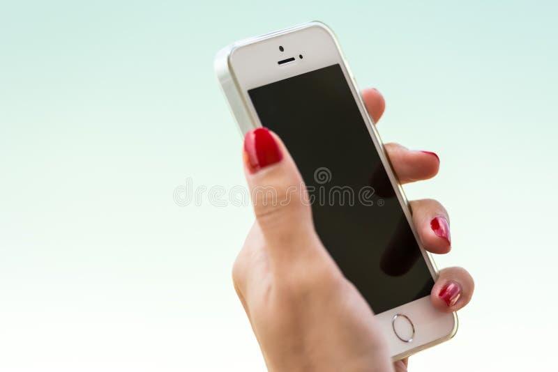 Рука женщины держа iPhone 5S Яблока стоковое фото