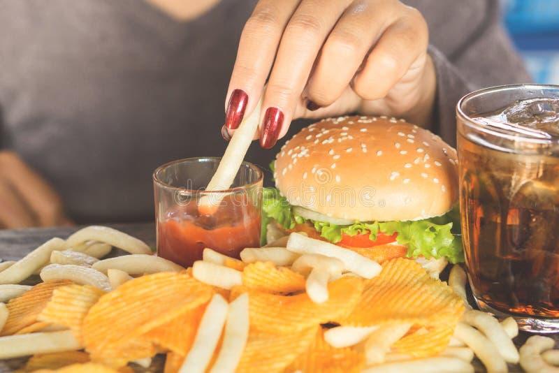 Рука женщины есть бургер фаст-фуда, картофельные стружки, фраи француза и сладостное питье на деревянном столе стоковое фото rf