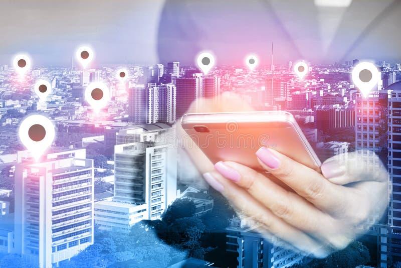 Рука женщины используя мобильный телефон с значком над умным городом, концепцией положения сетевого подключения стоковое фото