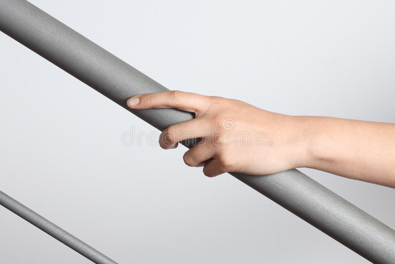 Рука женщины используя перила, который нужно пойти вверх стоковые изображения