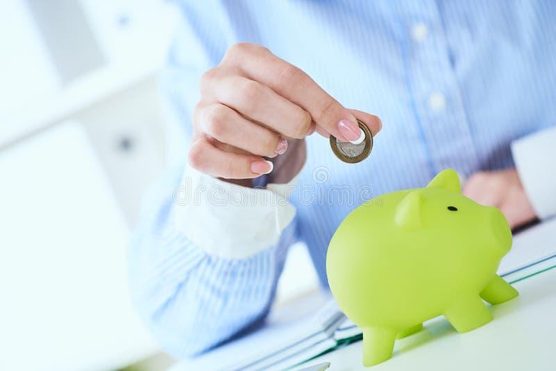 Рука женщины кладя монетку денег в зеленый конец-вверх копилки в предпосылке офиса Растя дело, пенсия и стоковое изображение rf