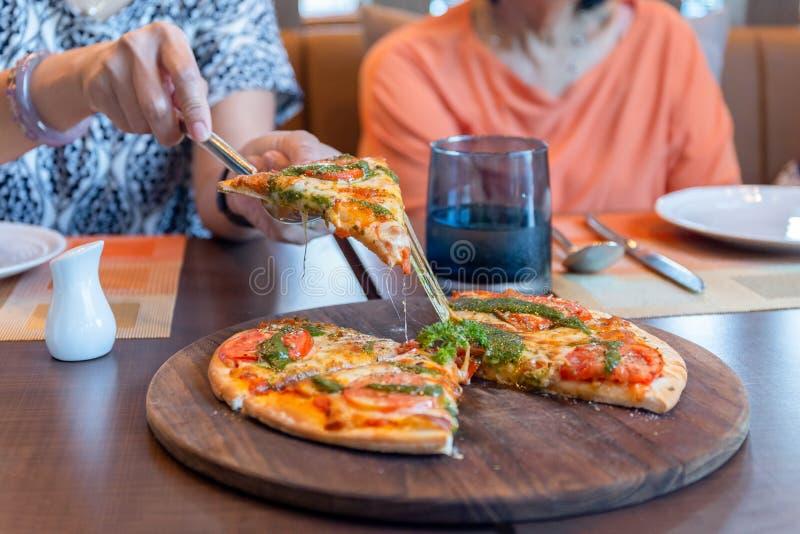 Рука женщины комплектуя часть пиццы на деревянной доске в ресторане стоковое фото