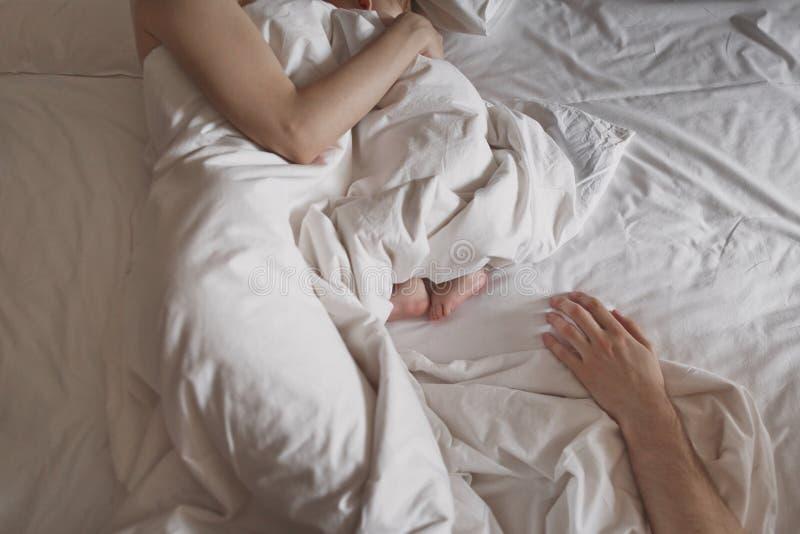 Рука женщины обнимает newborn младенца Рука ` s человека лежит наряду малыми ногами ` s детей на белой кровати Атмосфера стоковая фотография rf