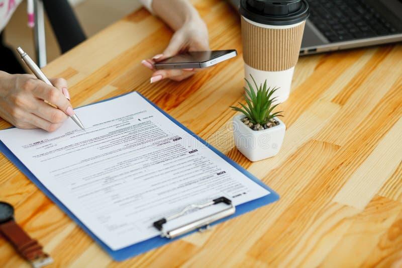 Рука женщины писать или подписывая внутри документ стоковое изображение