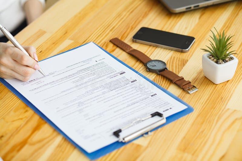 Рука женщины писать или подписывая внутри документ стоковые фотографии rf