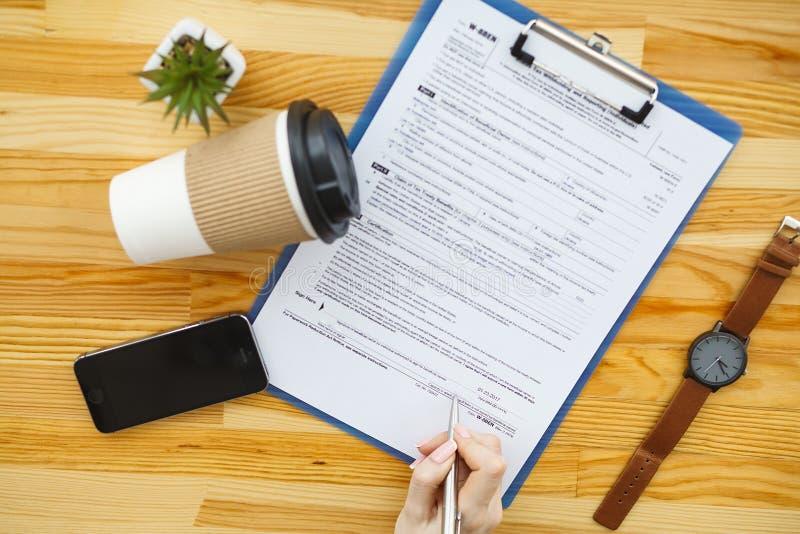 Рука женщины писать или подписывая внутри документ стоковые изображения rf