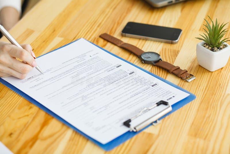 Рука женщины писать или подписывая внутри документ стоковое изображение rf