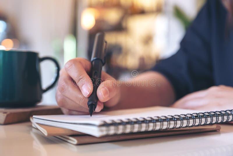 Рука женщины писать на пустой тетради с кофейной чашкой на таблице в кафе стоковые фотографии rf