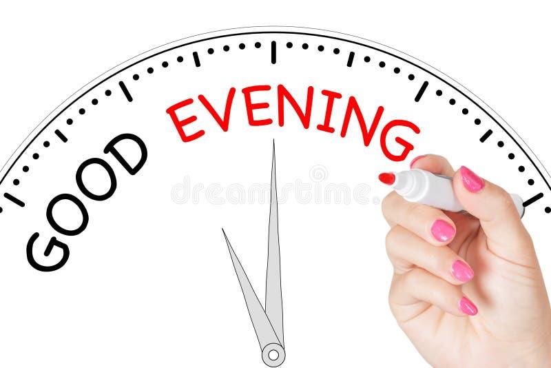 Рука женщины писать сообщение доброго вечера с красной отметкой на прозрачном обтирает доску r стоковое изображение