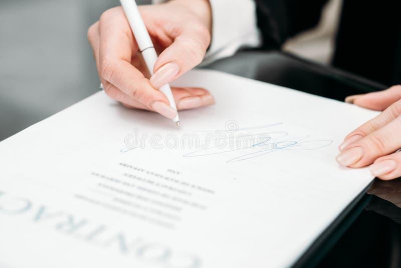 Рука женщины подписывает коммерческую сделку крупного плана контракта стоковое фото rf