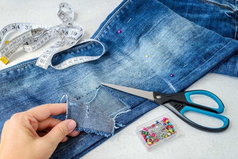 Рука женщины показывает большому отверстию на ноге тяжелого дыхания сложенные голубые джинсы в половине Джинсы подготовлены для р стоковые фото