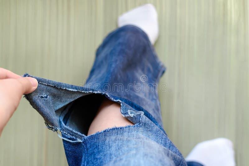 Рука женщины показывает отверстию на джинсы Женщина одетая в голубые джинсы с большим отверстием под коленом на левой ноге тяжело стоковое изображение rf
