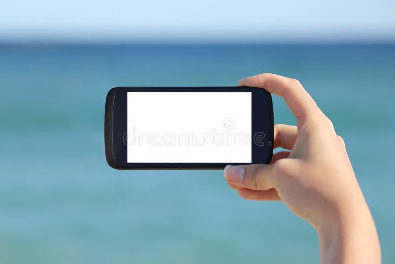 Рука женщины показывая пустому умному телефону горизонтальный экранный дисплей стоковое изображение rf