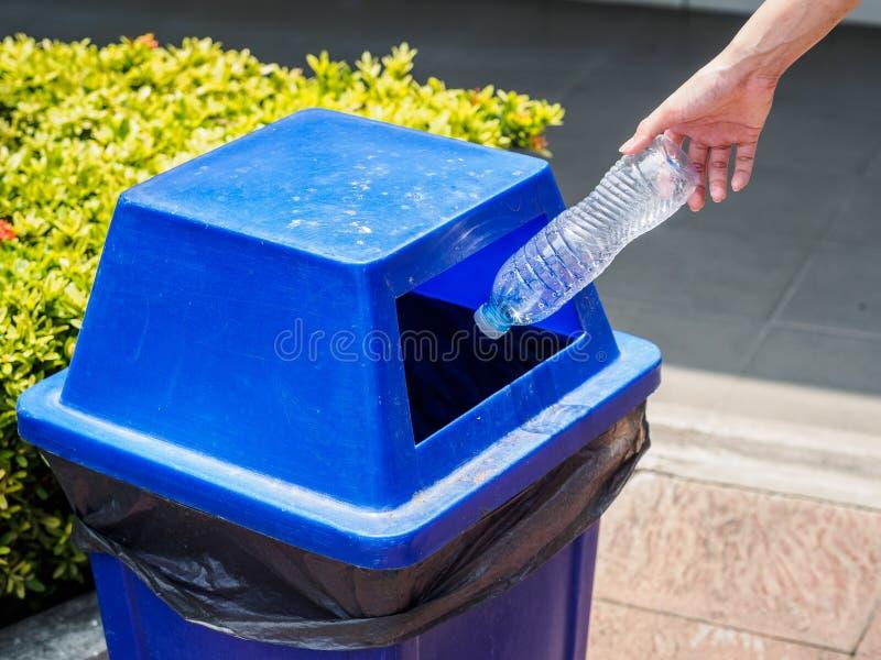 Рука женщины портрета крупного плана бросая пустую пластичную бутылку с водой стоковые изображения rf