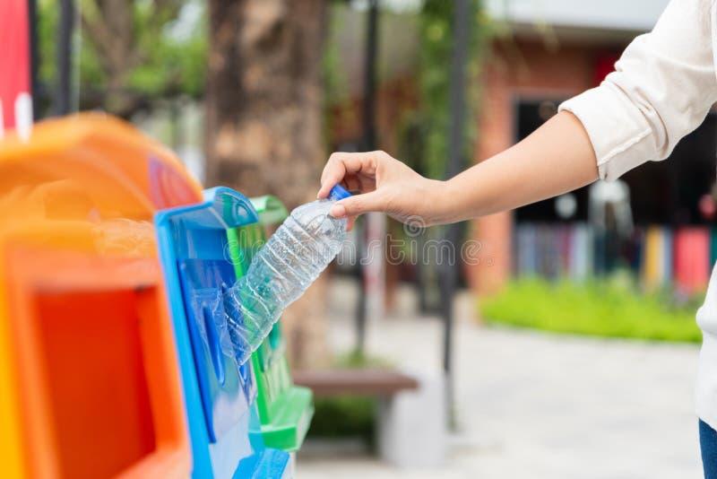 Рука женщины портрета крупного плана бросая пустую пластичную бутылку с водой в рециркулируя ящике стоковые изображения